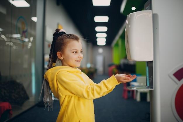 Kind meisje met automatische alcoholgel dispenser spuiten op handen ontsmettingsmiddel machine antiseptisch ontsmettingsmiddel nieuw normaal leven na coronavirus covid pandemie