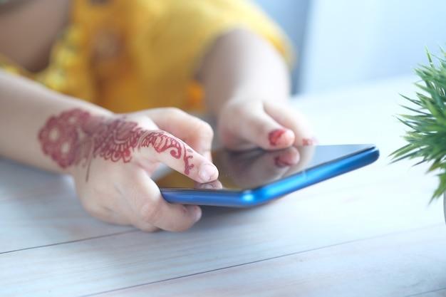Kind meisje met behulp van slimme telefoon op tafel