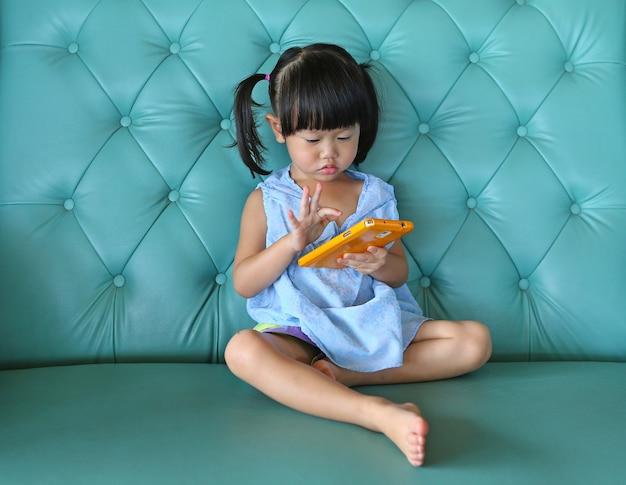 Kind meisje met behulp van slimme telefoon op vintage sofa