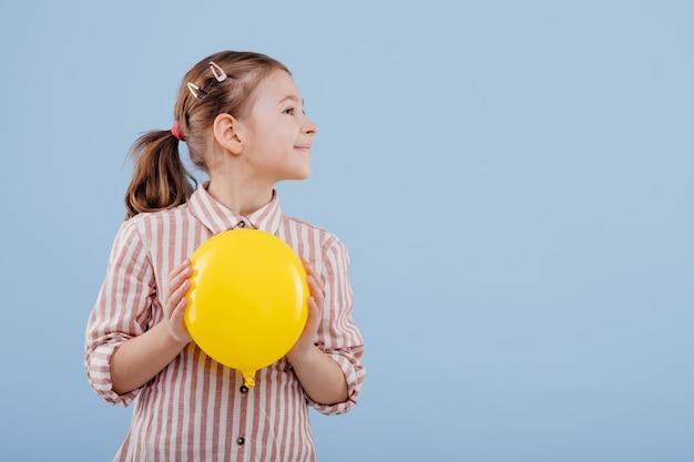 Kind, meisje met gele ballon kijk naar de zijkant, profielweergave, gekleed in gestreept shirt, geïsoleerd op blauwe achtergrond, kopieer ruimte