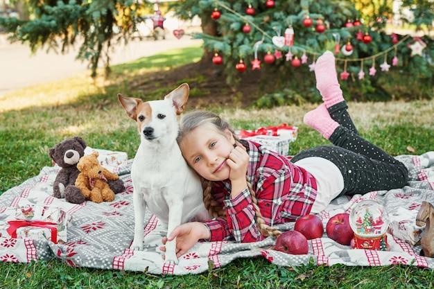 Kind meisje met hond jack russell terrier in de buurt van de kerstboom met geschenken,