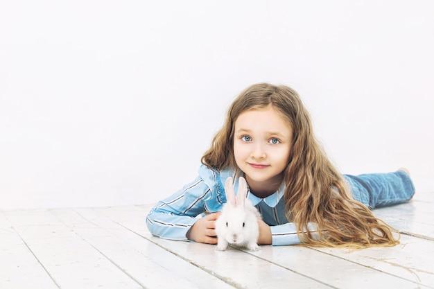 Kind meisje mooi schattig vrolijk en blij met klein dier konijn op witte muur achtergrond