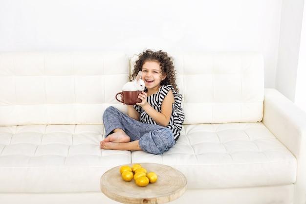Kind meisje mooi schattig vrolijk en blij met kleine dieren konijn en paaseieren thuis