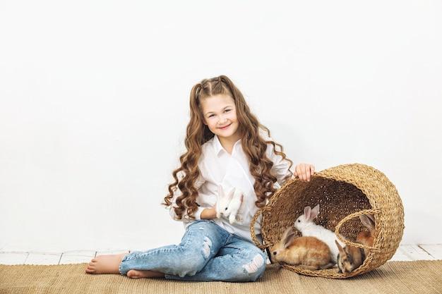 Kind meisje mooi schattig vrolijk en blij met kleine dieren konijnen op witte muur achtergrond