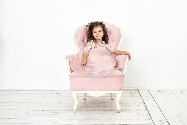 Kind meisje mooi, schattig vrolijk en gelukkig op een roze stoel in een modieuze luxe jurk