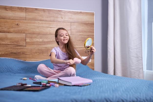 Kind meisje op bed spelen met moeders cosmetica. kaukasisch kind kijkt naar kleine spiegel