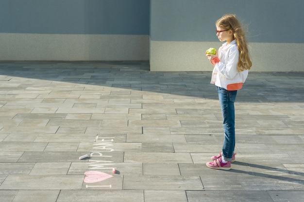 Kind meisje schreef op het asfalt ik hou van mijn planeet
