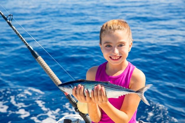 Kind meisje vissen tonijn bonito sarda vis blij met de vangst