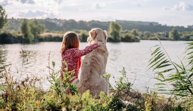 Kind meisje zit en knuffelt golden retriever hond buiten in de natuur en kijkt naar het meer...