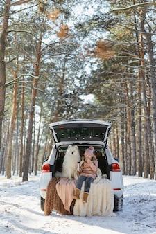 Kind meisje zit in de kofferbak van de auto met haar huisdier, een witte hond samojeed, in de winter in het besneeuwde dennenbos, een meisje dat thee drinkt uit een thermoskan