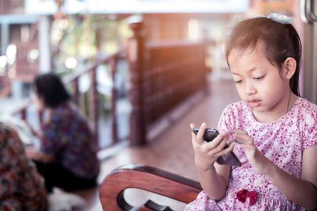Kind meisje, zittend op de smartphone terwijl de moeder op haar te wachten