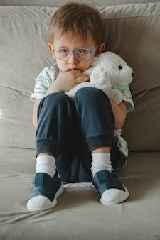 Kind met autisme met een bril zit op de bank en verdrietig