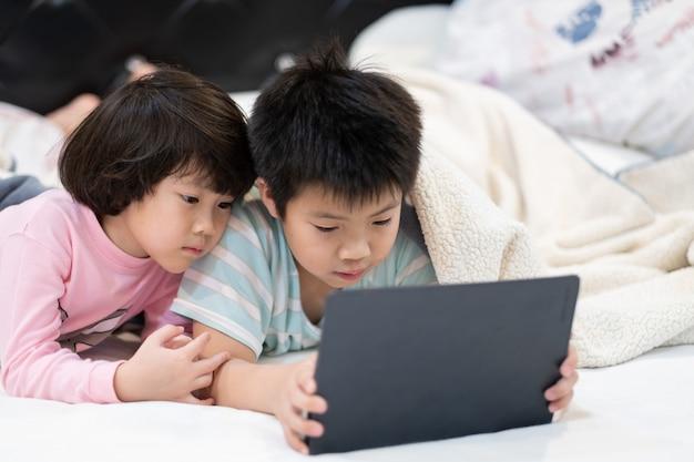 Kind met behulp van tablet samen op hun bed