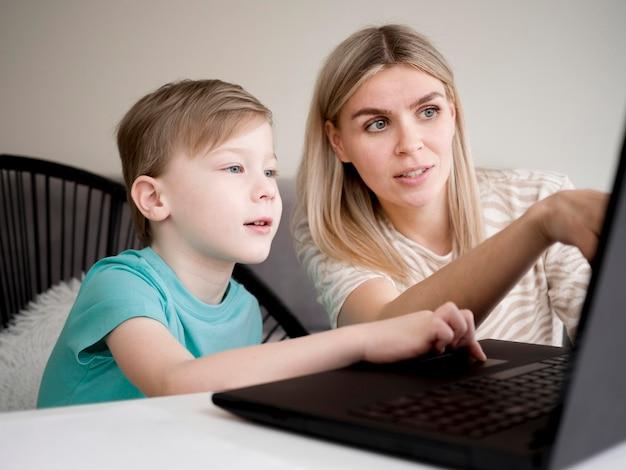 Kind met behulp van zijn laptop binnenshuis naast zijn moeder