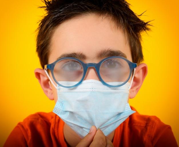 Kind met beslagen lens door gezichtsmasker voor covid-19 coronavirus op geel