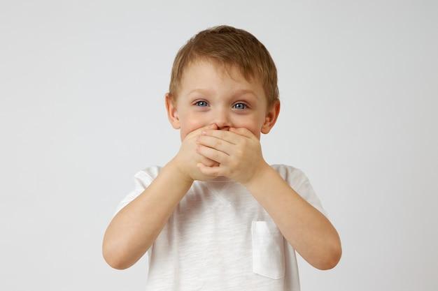 Kind met blauwe ogen houdt de emoties van vreugde tegen die zijn mond bedekt met zijn handen