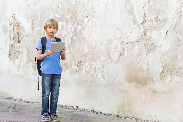 Kind met digitale tablet en rugzak in de stad straat