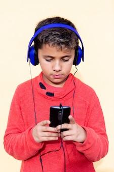 Kind met donker haar luisteren muziek met blauwe hadphones en een mobiel