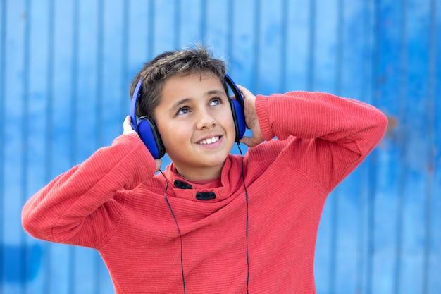 Kind met donker haar luisteren muziek met blauwe koptelefoon