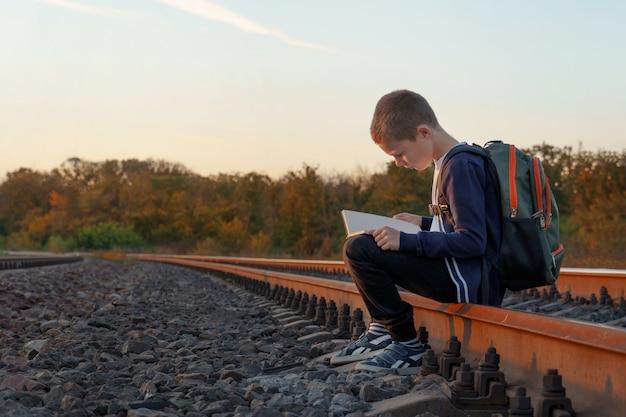 Kind met een boek in zijn handen op treinvluchten. jongen zit op vluchten en leest een boek tegen de ondergaande zon.