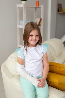 Kind met een gipsverband om een gebroken pols of arm die lacht en plezier maakt op een bank. positieve instelling
