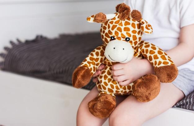 Kind met een giraffe knuffel op een grijze achtergrond
