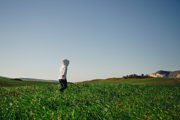 Kind met een kap loopt vrij in het gras