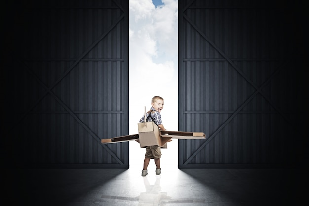 Kind met een kartonnen vliegtuig in de hangar