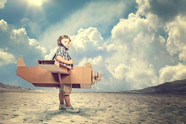 Kind met een kartonnen vliegtuig in een woestijn