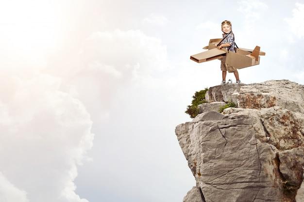 Kind met een kartonnen vliegtuig op een rots