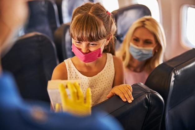 Kind met een medisch masker dat naar een chocoladepakket kijkt