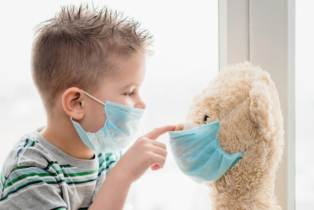Kind met een teddybeer zit in quarantaine tijdens coronavirus-pandemie