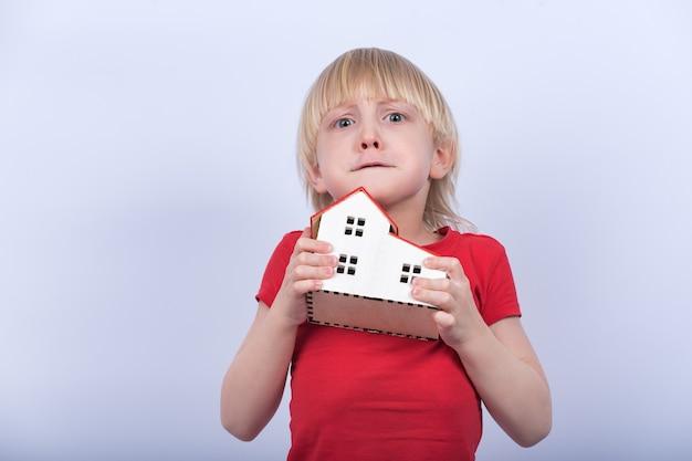 Kind met een verontrust gezicht houdt een model van een huis vast. onderdak, wees, adoptie.