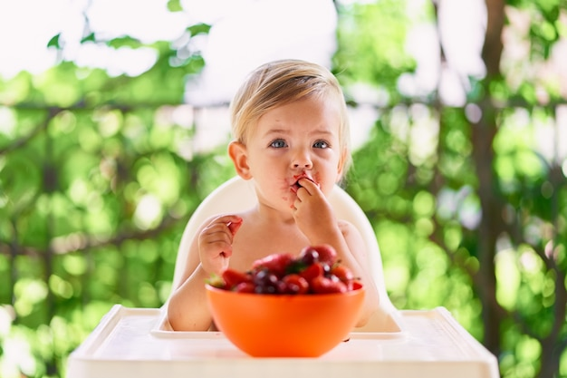 Kind met een vies gezicht zit aan tafel en eet kersen