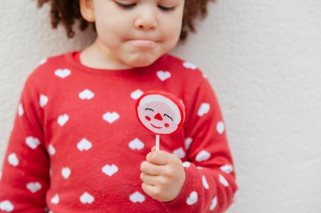 Kind met een weerhaar met een zoet snoepje