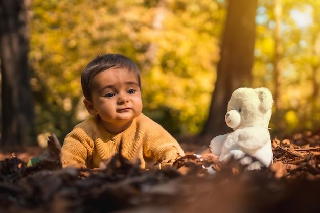 Kind met een witte teddybeer in het park op een zonnige herfstdag. natuurlijk licht, baby halverwege het jaar liggend op de bladeren van de bomen