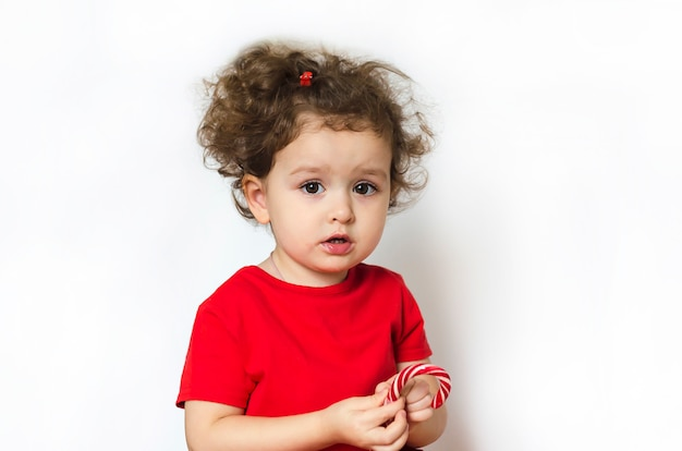 Kind met eetlust eet snoep. meisje met een lolly in haar handen. gelukkige jeugd.