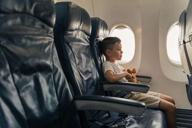 Kind met favoriet speelgoed zittend op vliegtuigstoel