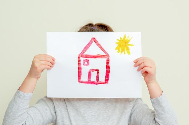 Kind met foto van huis.