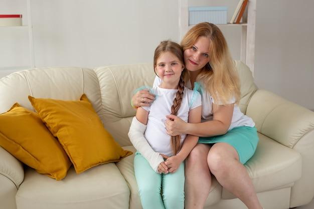 Kind met gebroken arm en gips tijd thuis met moeder doorbrengen. kinderziektes, een positieve
