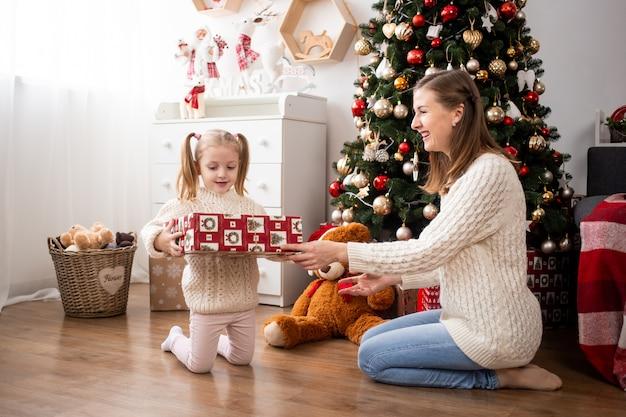 Kind met geschenkdoos en haar moeder thuis in de buurt van de kerstboom