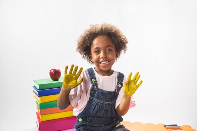 Kind met geschilderde handen in studio