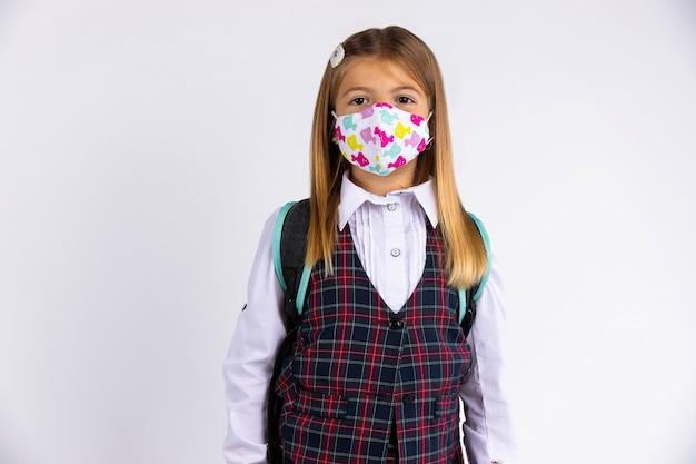 Kind met gezichtsmasker gaat terug naar school na covid-19 quarantaine en lockdown. geïsoleerd op grijze muur.