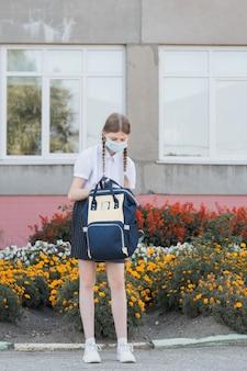 Kind met gezichtsmasker gaat terug naar school na covid-19 quarantaine en lockdown. terug naar school universiteitsstudent meisje met een covid-masker dat op de campus loopt met rugzak, boeken en laptop