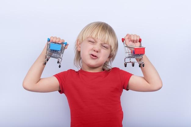 Kind met grappig gezicht dat twee stuk speelgoed boodschappenwagentje houdt. aankopen voor kinderen. baby winkelen