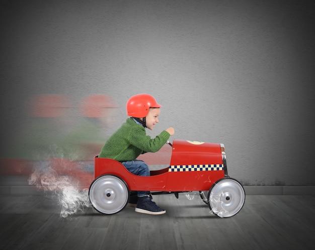 Kind met helm speelt met de auto