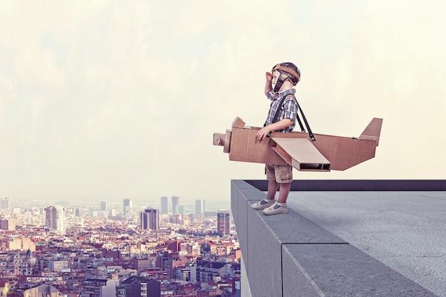 Kind met kartonnen vliegtuig op de top van het gebouw, de stad op de achtergrond