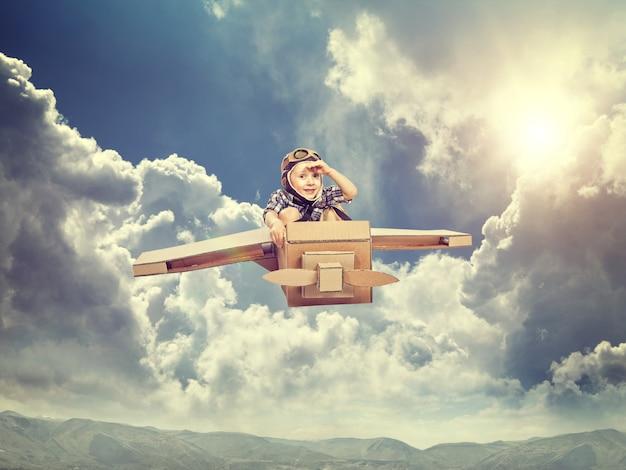 Kind met kartonnen vliegtuig vliegen in de lucht