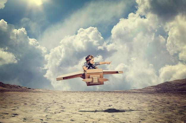 Kind met kartonnen vliegtuig vliegen over de woestijn