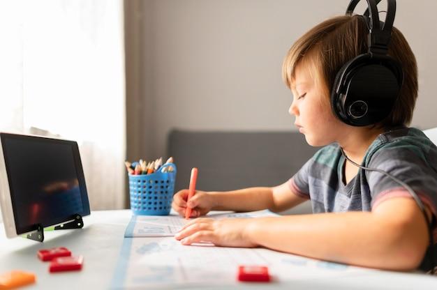 Kind met koptelefoon naar virtuele school